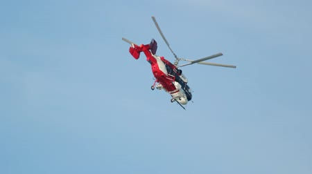 letec : Red helicopter flying down against a clear sky without clouds
