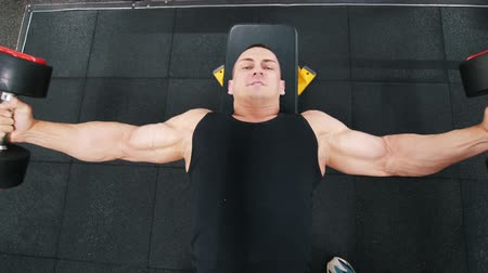 crossover : Bodybuilder in a black tank top performs a dumbbell fly exercise lying on a bench Stock Footage