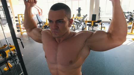 feszült : Bodybuilder with bare torso performs an overhead cable curl exercise in the gym Stock mozgókép