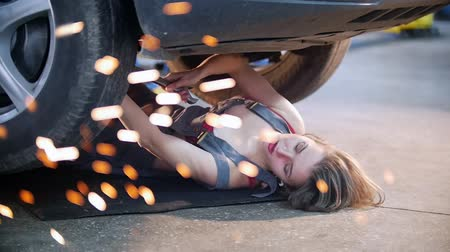 abriu : Sexy mechanic girl lying under the car and repairing it Stock Footage