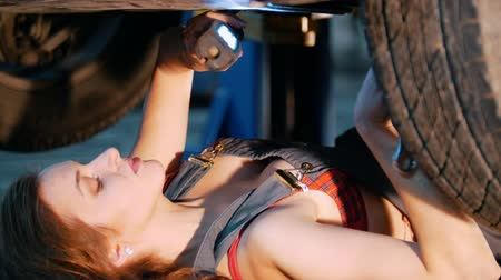 csavarhúzó : Sexy mechanic girl lying under the car and repairing it. Close up
