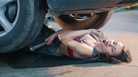 abriu : Sexy mechanic girl lying under the car and fixing it in slow motion Stock Footage