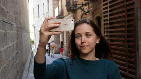 posando : Young girl standing at european street and taking a selfie