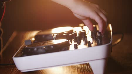 alaplap : Close up of hands of DJ plays music mixing and scratching on turntable music equipment. Professional music equipment with lights and controls being played by male disc jockey.