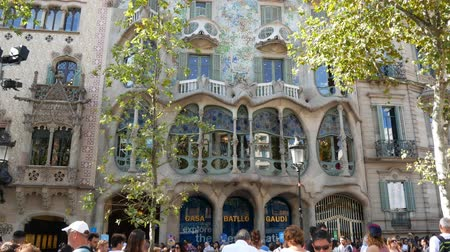 az érintett : Barcelona, Spain - September 2018: Casa Batllo facade, tilt up and down, few unidentified tourists in front of famous building. Art Nouveau architecture by Antoni Gaudi, recognizable landmark house