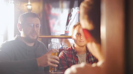 ale : Three young men sitting in the irish pub drinking beer Stock Footage
