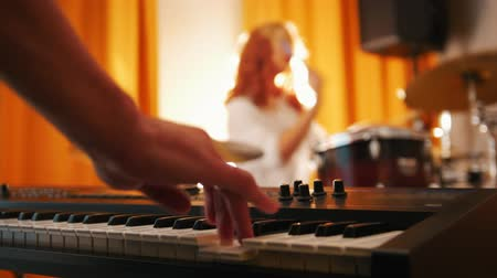 dobos : Repetition. Girl playing on drums and a guy on keyboards. Focus from hands to drums
