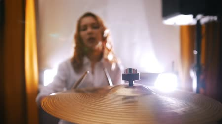 músico : Repetition. Redhead girl plays on drums. Slow motion. Focus on plate