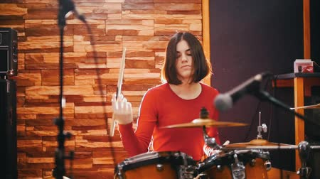 dobos : Repetition. Girl in red sweater passionately plays the drums Stock mozgókép