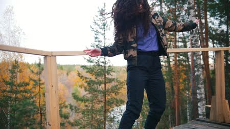 пальто : Smiling young woman dancing on platform. Flying hair. Forest on the background. Slow motion Стоковые видеозаписи