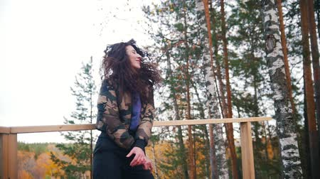 iyi seyir : Happy young woman dancing on high altitude and smiling. Flying curly hair. Forest. Stok Video
