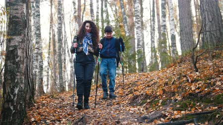 этап : Young woman and a boy on scandinavian walk in the forest. Going downhill.