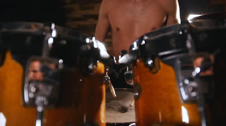 yüksek sesle : Shirtless drummer playing in studio. Drumsticks