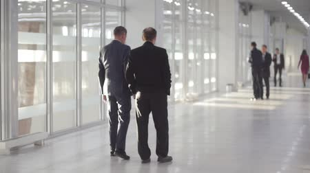 партнеры : Cheerful business people walking together along the office corridor and holding a conversation