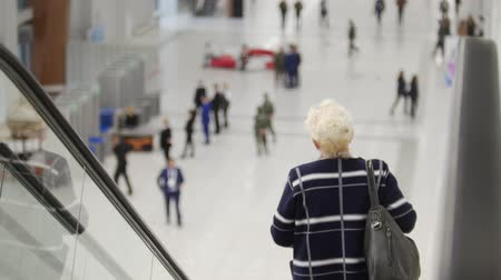 nanny holding : back view of escalator. Aged woman goes down.
