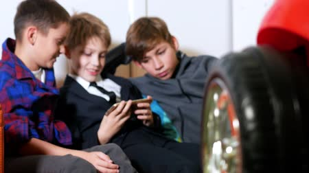 tongs : Three boys sit on sofa and playing videogames on mobile phone Stock Footage