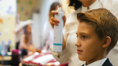 tongs : Stylist combs little boys hair with hairspray