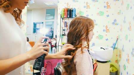 barber equipment : Stylist makes styling with hairspray for little cute girl Stock Footage