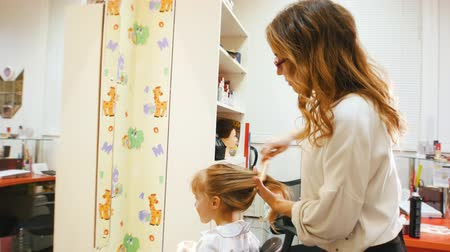 parrucchieria : Hairdresser combs hair for a cute girl. Filmati Stock