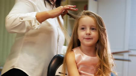 tongs : Hairdresser is curling long hair for little cute girl, using electric curling iron. Slider shot Stock Footage