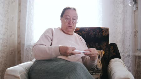 crochet : An elderly woman sitting in a chair and holds paper in hands on the background of the window.