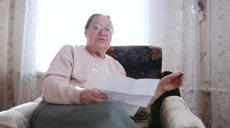 crochet : An elderly woman sitting in a chair and reading letter aloud on the background of the window. Stock Footage