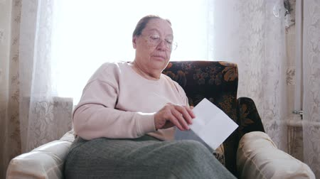 crochet : An elderly woman sitting in a chair and opens a letter on the background of the window. Stock Footage