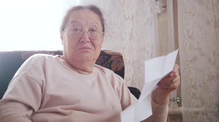 handig : An elderly woman reading letter while sitting in a chair on the background of the window. Stockvideo