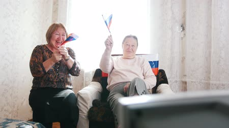 watching news : Two elderly women watching TV and waving Russian flags