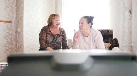 switching : Two elderly women watching TV and commenting Stock Footage