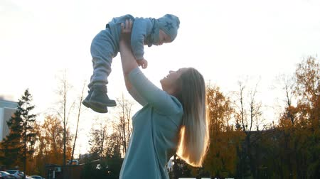 abilities : Young mother lifts up on hands her little baby. Happy family Stock Footage