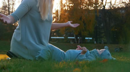 oddanost : Young mother with her baby playing in the autumn park on sunset. Baby lies on the grass. Happy family