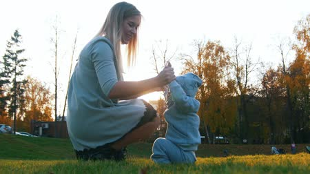 futuro : Young mother in dress with her little baby playing in autumn park. Happy family Stock Footage