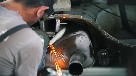 сварщик : The worker grinds the cut on the back of the car. Car repair service. Flying sparks