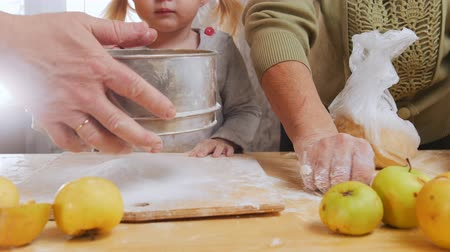 sifting : Family making little pies. Sifting flour. Little girl looking Stock Footage