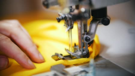 yorgan : Making clothes. Female hands work on Sewing Machine at studio. Slow motion shot