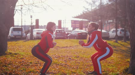 падение : Two young woman in sport costumes doing squats in park Стоковые видеозаписи
