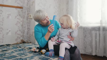 kartáč na vlasy : Grandmother brushing her granddaughters blonde hair with a hairbrush Dostupné videozáznamy