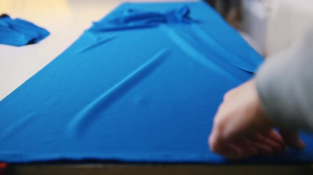kumaş : Worker at the clothing factory putting a blue cloth on the table