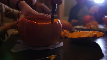 свечи : Halloween holiday party. A group of people cutting the pumpkin Стоковые видеозаписи