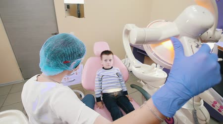 stomatologia : A little boy in the dentistry sitting in the patient chair, the dentist turns on the lamp and opening his mouth. Slow motion Wideo