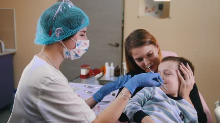 aberto : Dentistry. Female dentist tries to examine the teeth but the boy dont want to Stock Footage