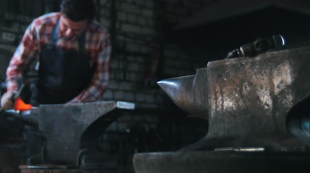 smith : Getting the red-hot detail a form with a hammer. Blacksmith in workroom, anvil