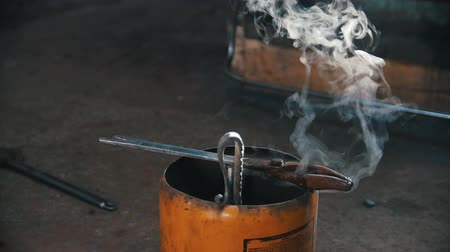 machado : Water evaporates from the forceps. Blacksmith workroom. Mid shot.
