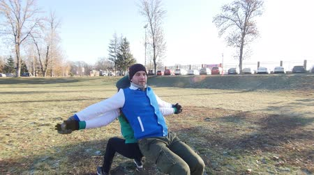 kaslar : Young man and a woman are warming up in late autumn park. Doing squats on open air back to back. Stok Video