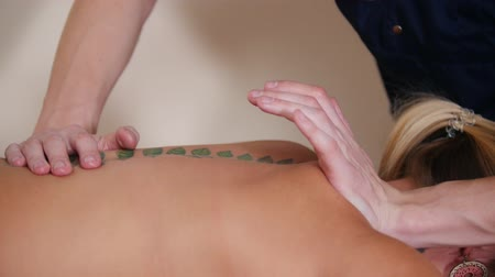 akupresura : Massage session. Young masseur doing acupressure on the top of a back. Back with a tattoo.