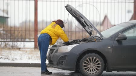 road sign : Car Trouble. Winter, cold weather. A young woman opens the hood, looking inside, rummaging in the engine, holding a phone Stock Footage
