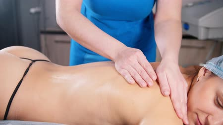 ás : A professional masseur massaging client s back and shoulders with oil in a light