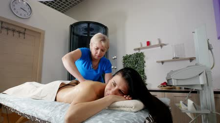 ayurveda : A professional masseur massaging beautful client s back and shoulders with care in a light. Relaxing massage