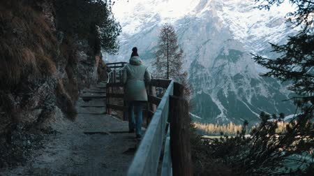 canon : Dolomites. Mountain road. A woman walks upwards holding onto the railing